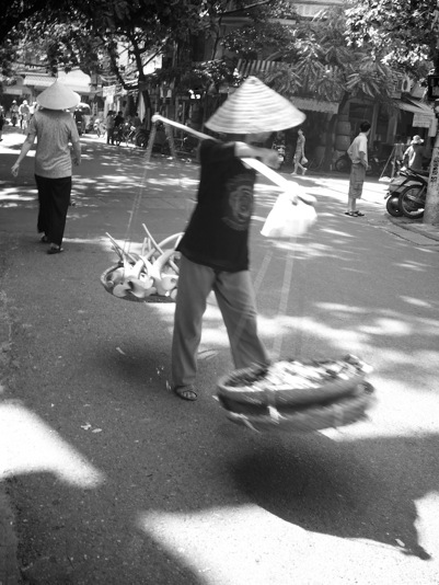 B&W street image of Hanoi street seller with conical hat